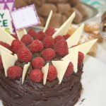 Cake decorated with white chocolate shards and raspberries